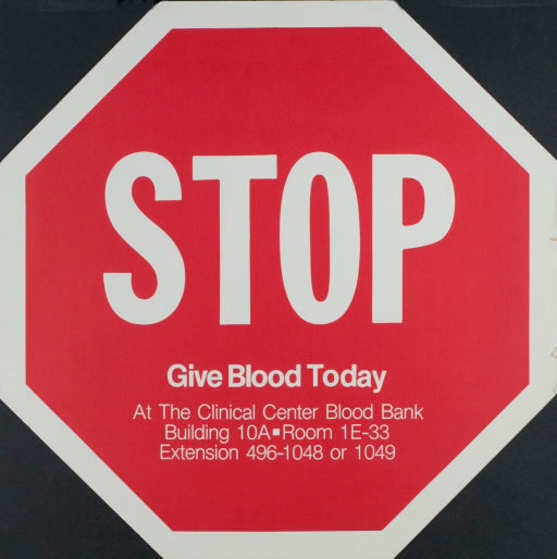 <p>Red and white poster shaped like a stop sign. The print is in white and the details on when and where to give blood are listed at the bottom of the poster.</p>