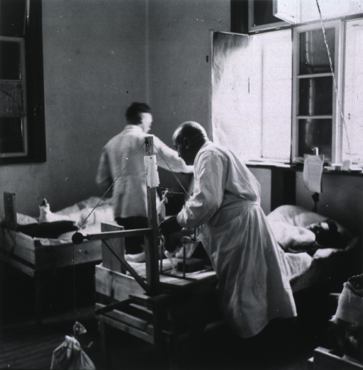 <p>Standing, back to photographer, adjusting a traction device in a hospital ward.</p>