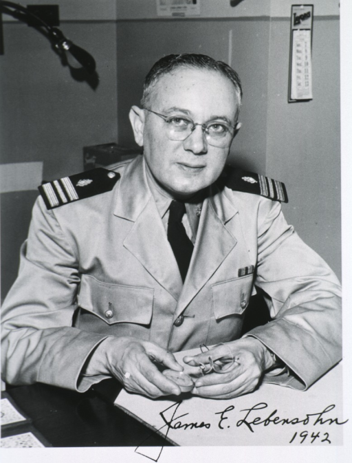 <p>Half-length, seated at desk, full face; wearing uniform and glasses.</p>