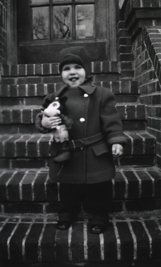 <p>A little boy, holding a toy, stands on the front steps.</p>