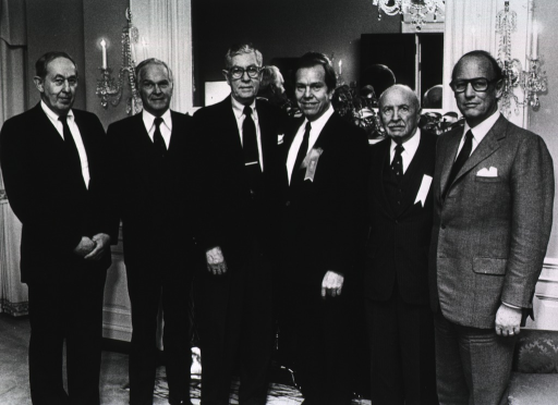 <p>Past and present directors of the National Institutes of Health gathered at the Stone House on the occasion of renaming Building 1 to the James A. Shannon building.  Standing in front of a fireplace are Drs. Robert S. Stone (1973-1975), Robert Q. Marston ( (1968-1973), James A. Shannon (1955-1968), James B. Wyngaarden (1982-1989), Henry Sebrell, Jr. (1950-1955), and Donald S. Fredrickson (1975-1981).  Dr. Fredrickson is standing next to a sofa.</p>