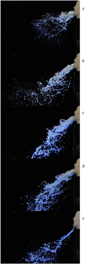 Images (a–-e) are sequential photographs of simulated vomiting taken 10 ms apart under UV light.a: Release of droplets prior to main bulk fluidb: 'Strings' of fluid and droplet falloutc: Mid flow of fluidd: Less droplet formatione: Fluid travelling less far towards end of simulation