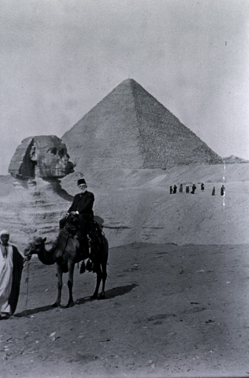 <p>Wearing a fez and sitting on a camel in front of the Sphinx.</p>