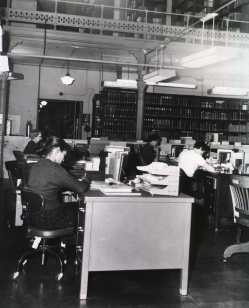 <p>Interior view: Staff members are sitting at their desks; one staff member is smoking a cigarette; books on shelves are in the background.</p>