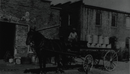 <p>Privy can stacked up on a horse-drawn wagon; a young boy sits on the driver's seat; brick buildings in the background.</p>