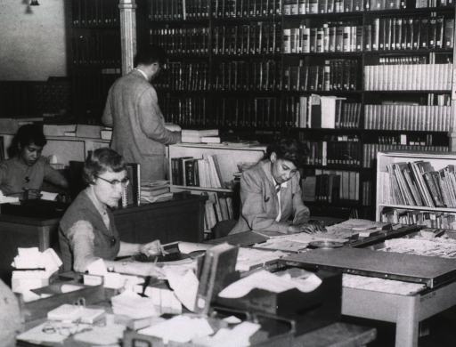 <p>Interior view:  Four staff members, two seated at desks, one at a tub file, and one standing by shelves; books on shelves are in the background.</p>