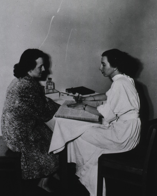 <p>Two women sit at a small table; the woman on the right records the medical history (?) of the woman applying for a visa.</p>