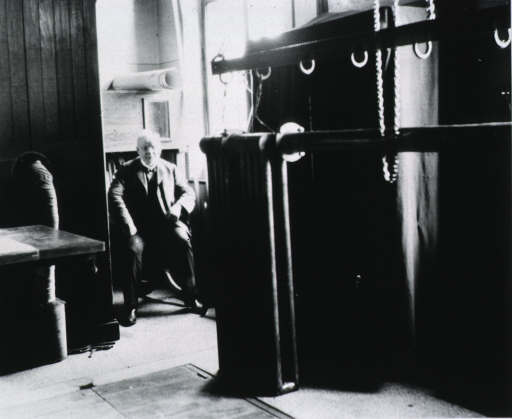 <p>Full length, seated in chair in laboratory, Bonn, Germany.</p>