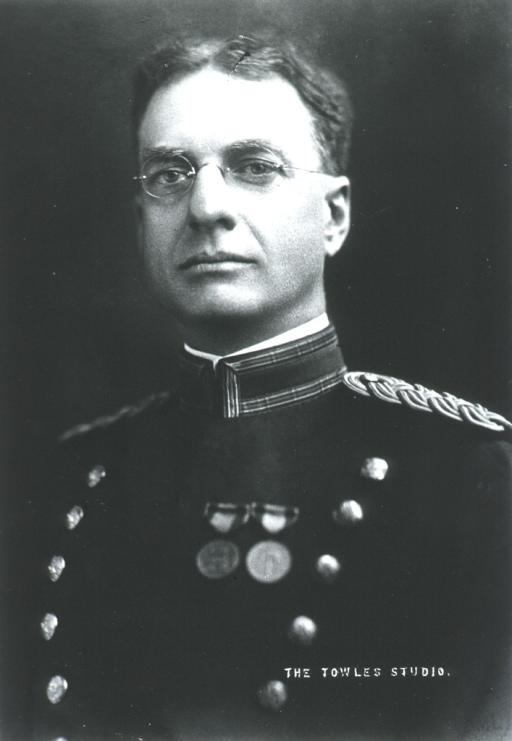<p>Head and shoulders, left pose, full face; wearing uniform (with two medals) and glasses.</p>