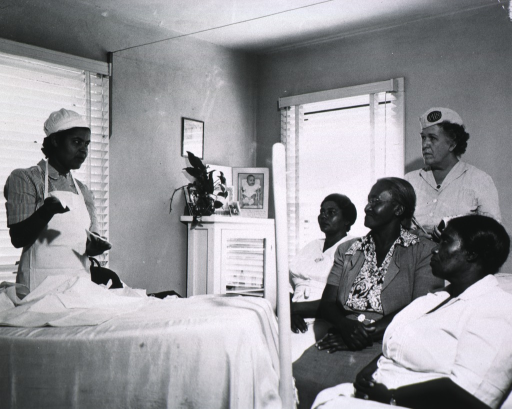 <p>Ethel Kirkland, an African American registered nurse, is teaching a Public Health Nurse and her small class of lay midwives in a typical County Health Department class setting.</p>