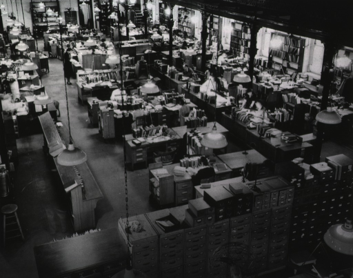 <p>The cataloging area of the Armed Forces Medical Library.  In the lower left, photographic technology produces the &quot;ghostly&quot; image of a man studying under a hanging light.</p>