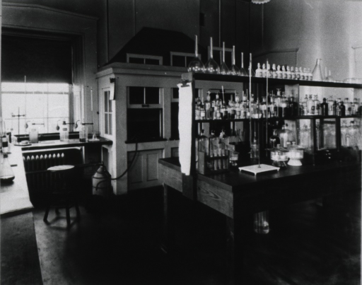 <p>Interior view of chemical laboratory; table with shelves of glassware; bench along the wall to the left and in the rear.</p>