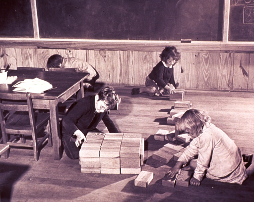 <p>Children are playing on the floor with blocks.</p>