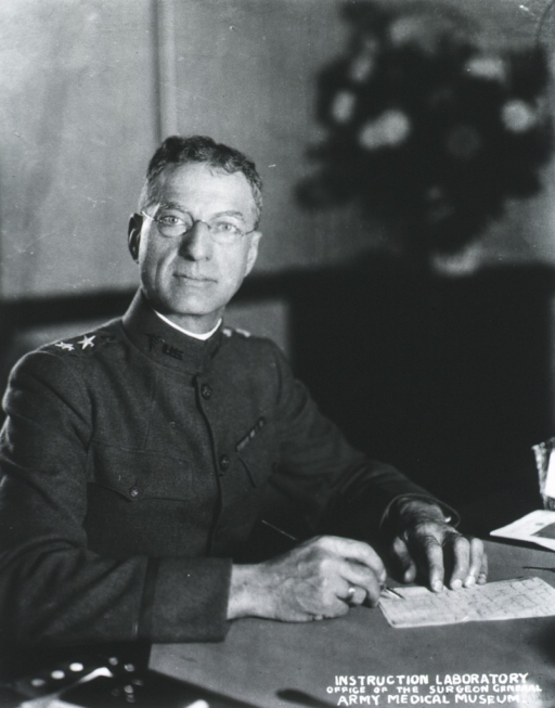 <p>Half-length, seated at desk, right pose, full face; wearing uniform and glasses; writing.</p>