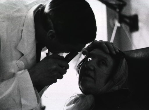 <p>A physician using an ophthalmoscope is examining a woman's eyes.</p>