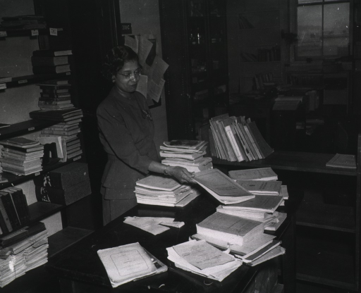 <p>Interior view:  Woman staff member sorting publications; material is on the table, a book truck, and shelves.</p>