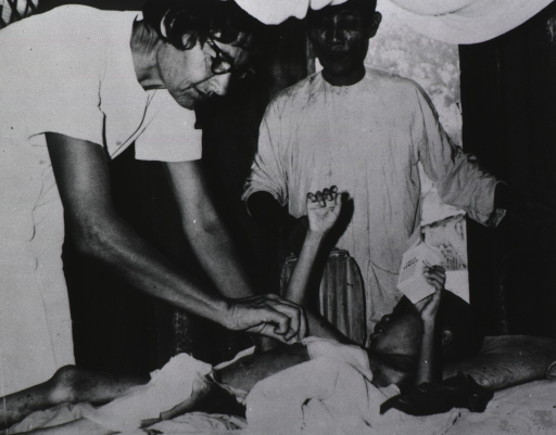<p>Nurse Turner attends to the bandages of a small child lying on a bed as an elderly male attendant looks on.</p>