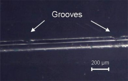Picture showing two consecutive unsymmetrical changes in the cladding thickness produced by MIR CO2 laser irradiation of a Corning SMF-28 fiber. (Cylindrical lens, exposure time 40 ms, 9 W laser power).