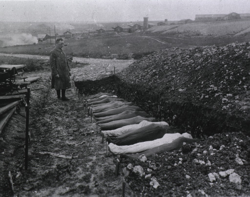<p>Chaplain T.R. White is standing before mass burial site for soldiers that died while at Red Cross Hospital no. 114 at Fleury sur Aisne, Meuse, France.</p>