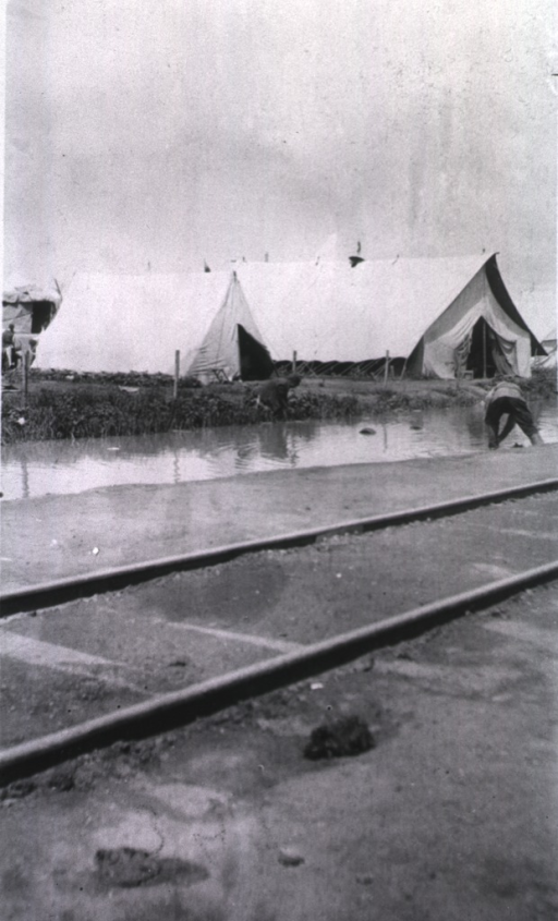 <p>A view of tents at Vitebsk Red Cross Hospital.  Two soldiers(?) lean into the water.</p>