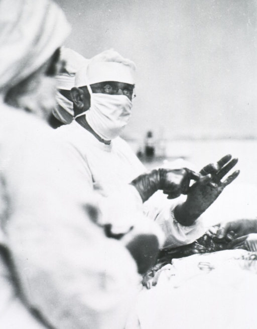 <p>Half length, turned slightly to right; in surgical gown, mask, cap, and gloves; lecturing in operating room.  Standing with assistants; patient on operating table.</p>