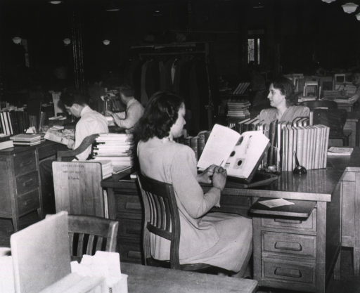 <p>Interior view:  Helen Field and others are looking at material; Catalog Division Subj. Cat. Sect. A. Roberts is written on a book truck stacked with material; cataloger in the foreground is reading a book that is resting on a stand; coats are hanging on a rack in the background.</p>
