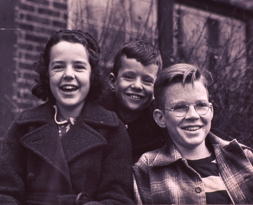 <p>Bust portrait, facing front, of two boys (left) and a girl (right) smiling; one boy (left) is wearing eyeglasses.</p>