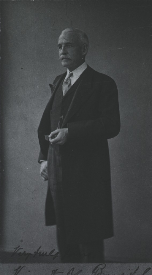 <p>Standing, left pose, right thumb hooked in right pocket, holding monocle in left hand, wearing long coat.</p>