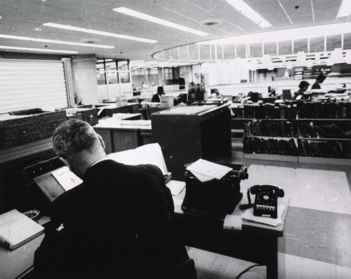 <p>Interior view: In the foreground is a man working at a desk.  On the desk is a multi-line telephone, a manual typewriter, and a book stand.  There is a shelf with index cards above the desk.  In the background are low book shelves, book trucks, and women working.</p>