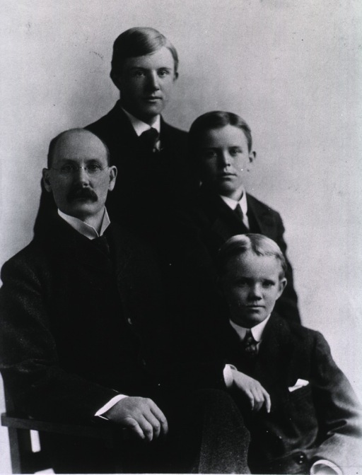 <p>Half-length, full face, seated in chair with his three sons standing beside him.</p>