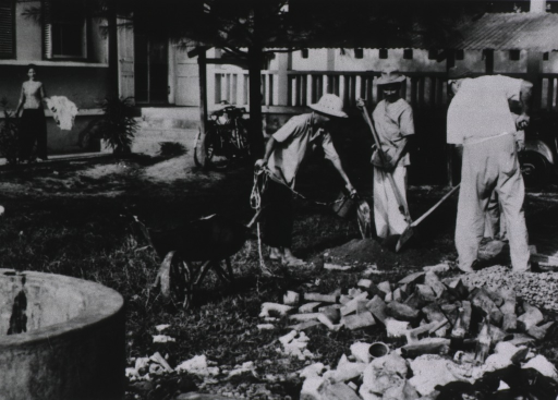 <p>Dr. Brooks, with shovel in hand, assists two workers in the construction of a platform for a new well to provide water for the hospital.</p>