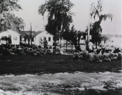 <p>Large group of women sitting on the ground; buildings in the background.</p>