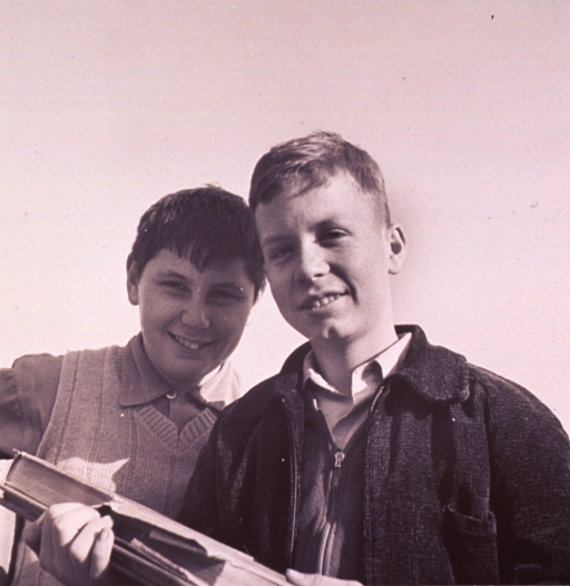 <p>Two boys, smiling (half-length portrait, facing front);  one boy is holding books.</p>