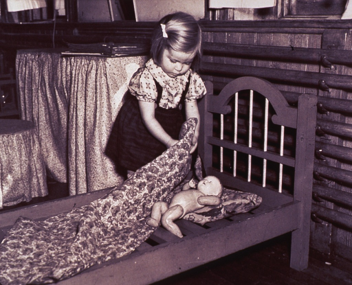 <p>A little girl is putting her doll to bed at a WPA nursery school in St. Paul, Minnesota.</p>