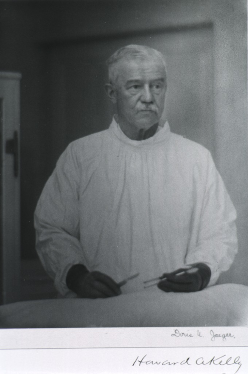 <p>Half-length, standing, full face; wearing operating gown and holding instruments in rubber gloved hands.</p>
