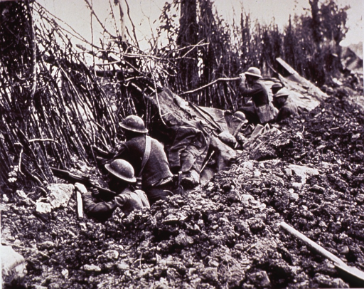 <p>Seen from the left and slightly to the rear, a line of soldiers waiting in a trench are peering through a wall of low plant growth; one man is looking through binoculars.</p>