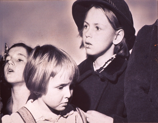 <p>Three girls (head-and-shoulders portrait); girl in center, foreground is facing right, two girls in background, one dressed in a hat and coat, are facing left.</p>