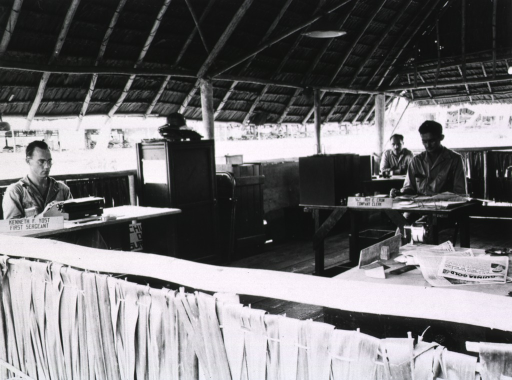 <p>Several servicemen are shown at work (typing, handling papers) in an open-air building with a thatched roof.</p>