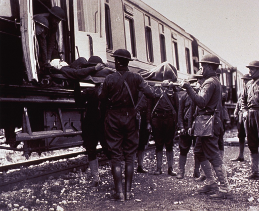 <p>A group of soldiers load patients onto a hospital train.</p>