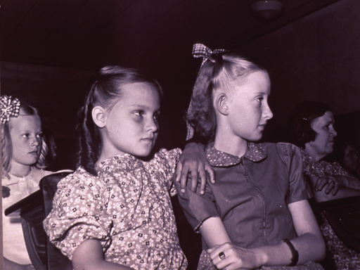 <p>Three girls seated, facing right; an adult  woman is visible in the right background (Adrian, Oregon).</p>