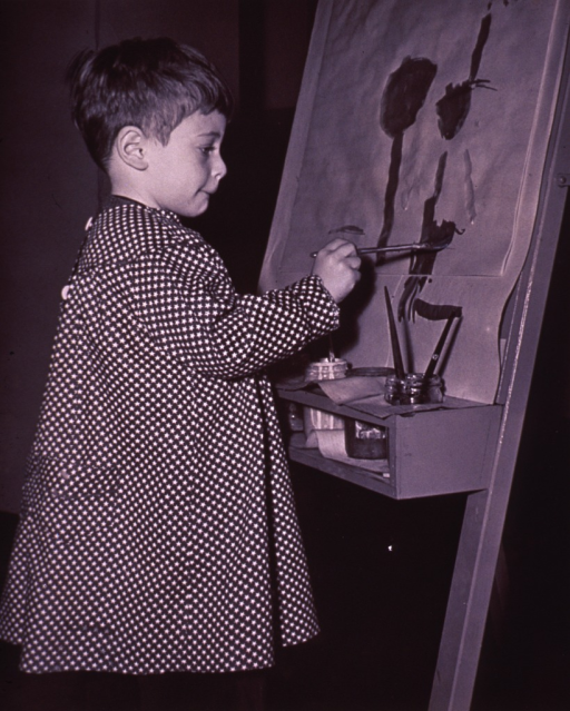 <p>A little boy is painting.</p>