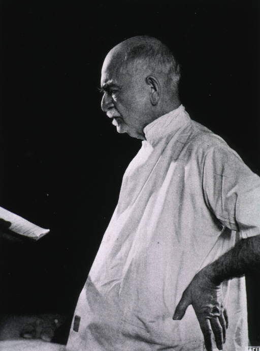 <p>Standing, left profile, hand on hip, wearing white smock.</p>