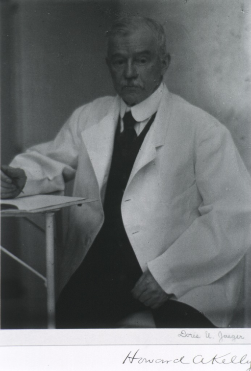 <p>Three quarter-length, seated, full face; wearing white coat; holding pen.</p>