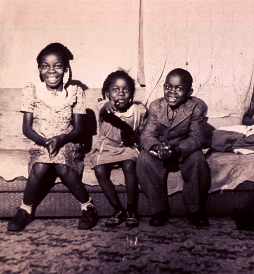 <p>Three African American children, two girls and a boy, are sitting on a sofa at the Flanner House; the girl in the center is pointing forward.</p>