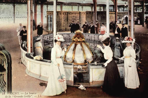 <p>Shows people standing at the fountain, La Grande Grille, in Vichy, France, and drinking the water.</p>