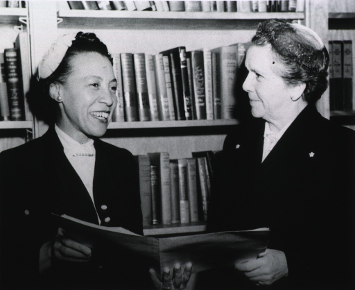 <p>Two of the board members, holding a document, standing in front of a bookcase.</p>
