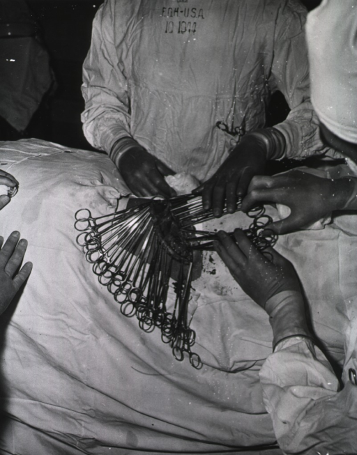 <p>Overhead view of the operative field of thoracic surgery performed on an unidentified and obscured person.  The doctors' faces are not visible.  Printed on the front of one doctor's surgical gown: &quot;10 1944.&quot;</p>