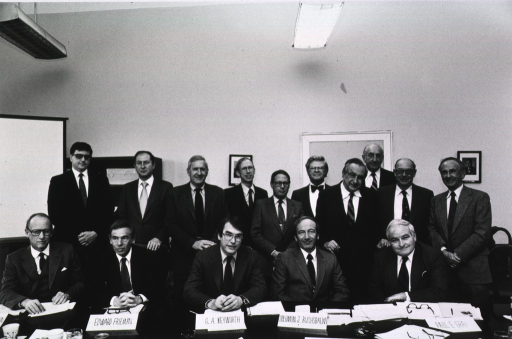 <p>The White House Science Council is assembled in a rather stark room with fluorescent lighting.  Seated at the table are Dr. Donald S. Fredrickson, Edward Allan Frieman, executive vice president and group manager for Science Applications International Corp., George A. Keyworth, of the Office of the White House Science Advisor, Solomon J. Buchsbaum, senior vice president of technology systems at AT&amp;T Bell Laboratories, and Paul E. Gray, president of the Massachusetts Institute of Technology.  Standing behind them are Robert Hunter, Arthur Karmin, Harold Agnew, director of the General Atomic Co., Edward E. David, president of Exxon Research and Engineering Co., D. Allan Bromley, assistant to the president for science and technology, Edward Teller, emeritus director of the Lawrence Livermore National Laboratory, David Packard, chairman of the board of the Hewlett-Packard Co., John Bardeen, professor emeritus University of Illinois, and George Cowan, Los Alamos associate director for research and senior laboratory fellow.</p>