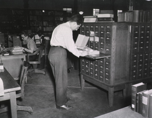 <p>Interior view:  Subject cataloger Charles Colby is at the card catalog, bookshelves are against the far wall.</p>