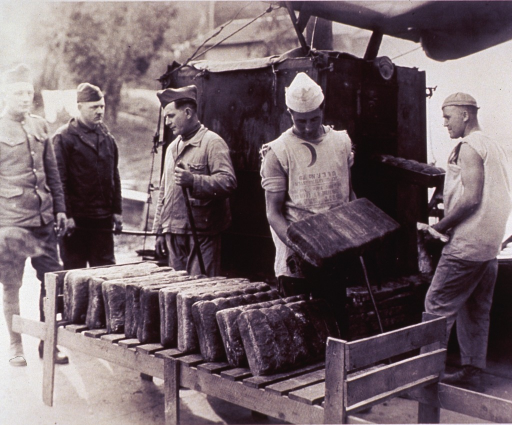 <p>A soldier places a block of bread loaves on a wooden rack to cool, behind him another soldier removes a tray of loaves from the outdoor oven; they wear shirts made from flour sacks; three soldiers stand to the left.</p>